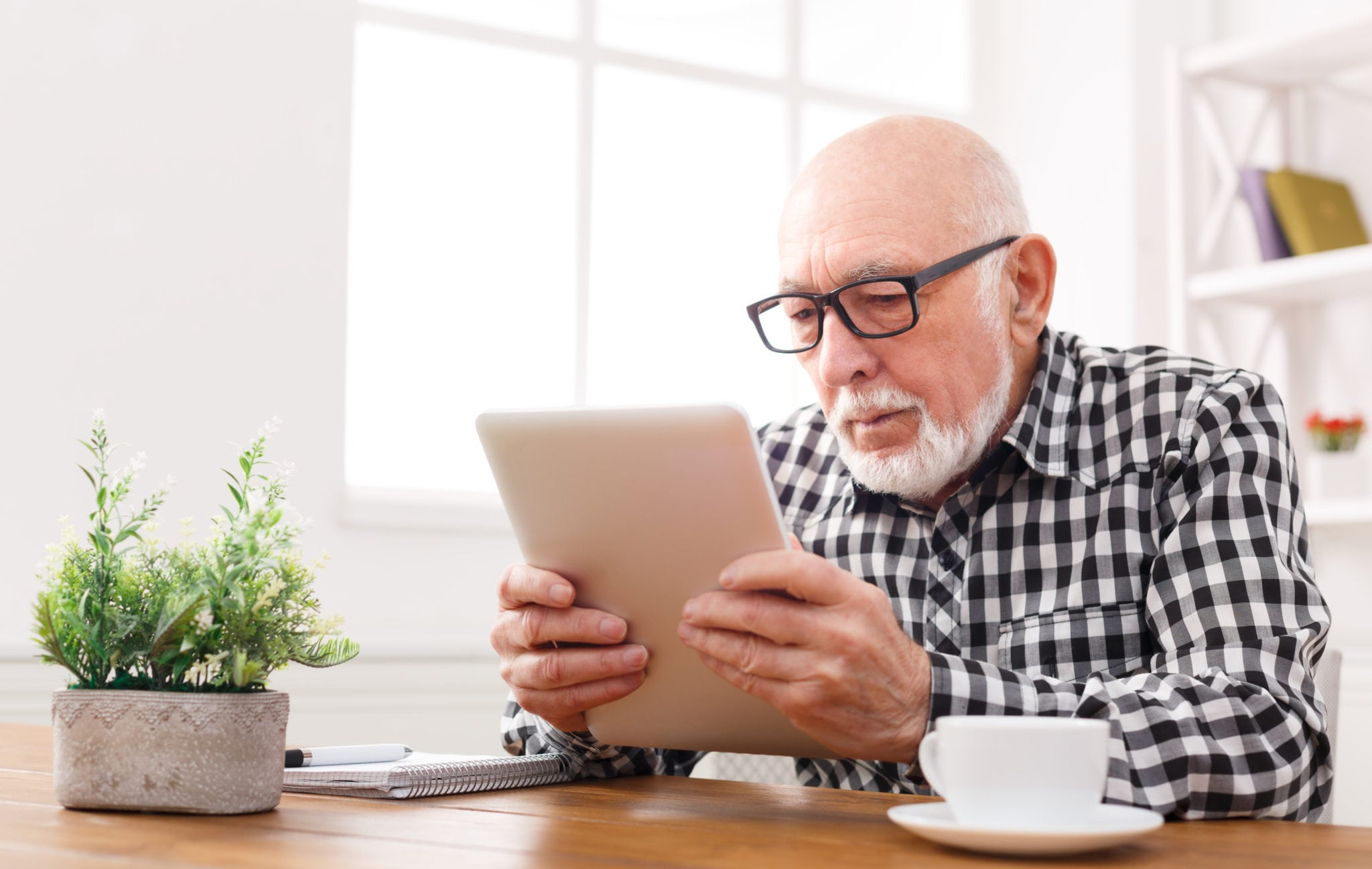 Senior man reading news on digital tablet | North Houston Hearing Solutions