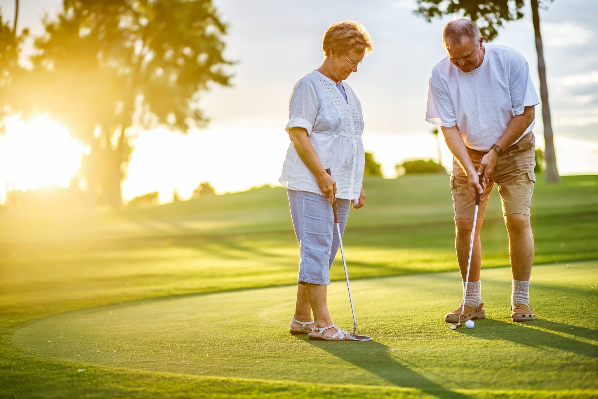 active senior lifestyle, elderly couple playing golf together at sunset|North Houston Hearing Solutions