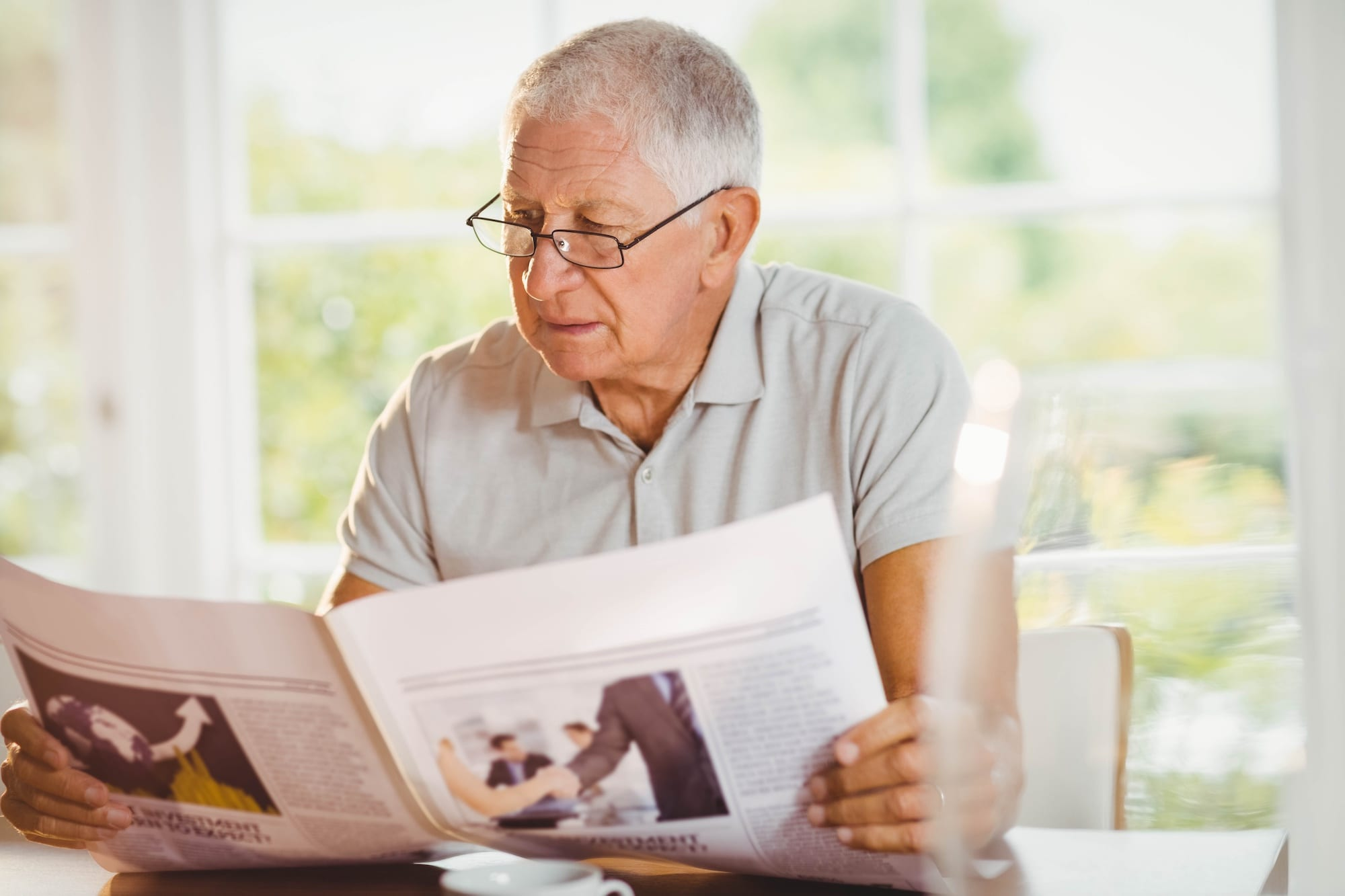 Focused senior man reading newspaper | North Houston Hearing