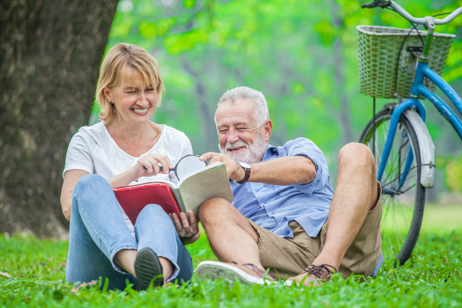Happy elderly couple with smiling face enjoying together, reading a book with magnifying glass in the park, spending time and relaxing time concept. | North Houston