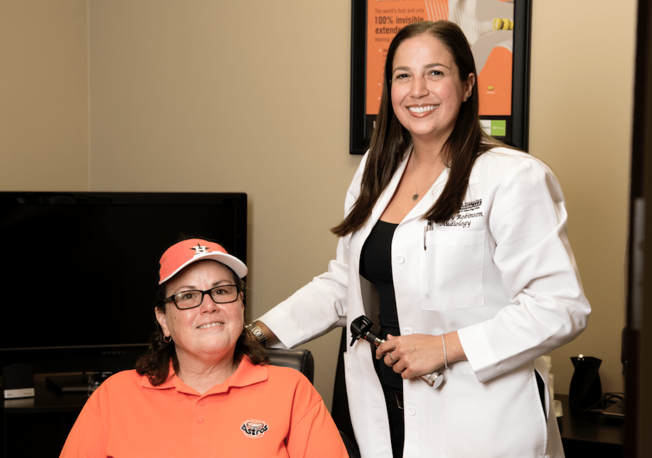 audiologist and patient smiling at camera
