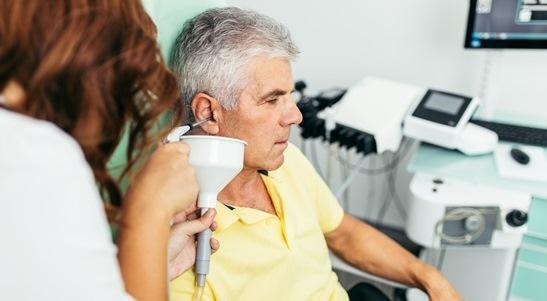 older gentleman having his ears cleaned by an audiologist
